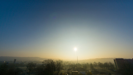 Sunrise at foggy morning in small city