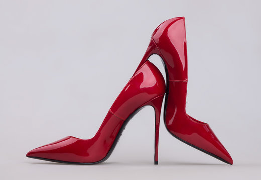 Women's red shoes with a varnish on a gray background