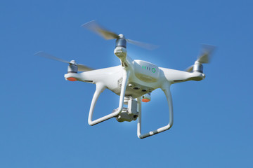 Drone quad copter with high resolution digital camera on the sky .White drone with digital camera flying in sky over mountain Drone with high resolution digital camera.