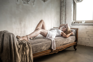 Portrait of a beautiful young woman laying on a antique Sofa.