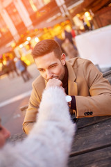A handsome young man sitting in a christmas market and kissing his girlfriends hand.