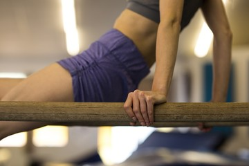 Sportswoman exercising on gym bar at fitness studio