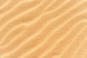 Sand texture on the beach with waves as natural tropical background