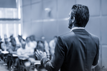 Rear view of speaker giving a talk at business meeting. Audience in the conference hall. Business and Entrepreneurship concept. Black and white blue toned image.