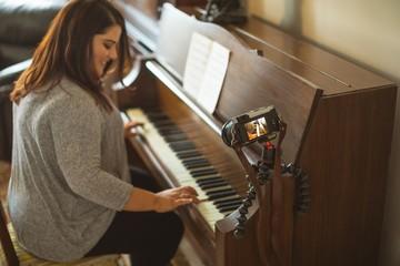 Beautiful female vlogger playing piano