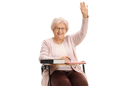 Mature woman holding her hand up sitting in a school chair