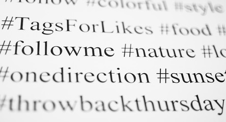 Closeup of typed popular hashtags. Words on the paper sheet. Abstract concept of social media, communication, social networking, digital society, and internet.