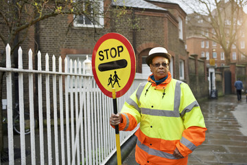 Portrait of crossing guard holding stop sign