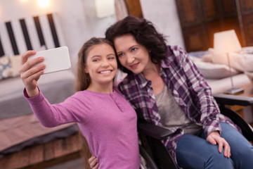 Just smile. Exuberant girl carrying phone while crippled woman embracing her