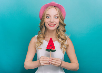 Girl with pink hat is standing and holdng an ice cream. It has colors of watermelon. She is looking straight and smiling. Isolated on blue background.