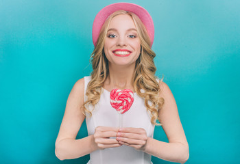 Beautiful and cheerful girl is standing and holding a lollipop in her hands. She is smiling. Isolated on blue background.