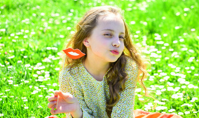 Kiss concept. Girl on kissing face spend leisure outdoors. Girl sits on grass at grassplot, green background. Child posing with cardboard smiling mouth.