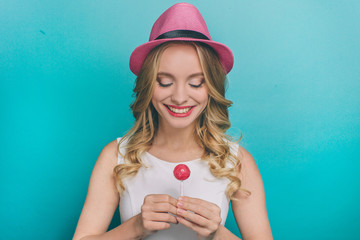 Lovely young person is holding a small pink lollipop in her hands. She is looking at it and smiling. Girl is happy. Isolated on blue background.