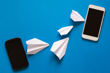 Data transfer concept. Message passing. Two mobile smartphones and paper airplanes on blue background. Origami. Paper cut.