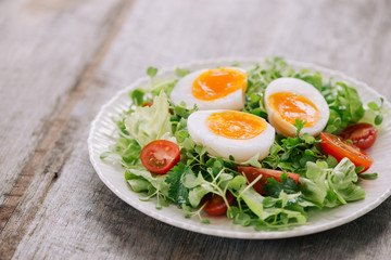 High Angle View of a Nutritious Vegetable Salad with Boiled Egg Slices, Served on a White Plate on Top of a Wooden Table