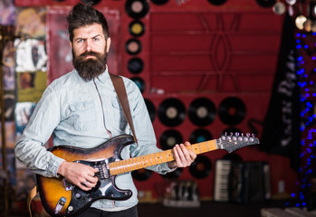 Musician with beard play electric guitar. Rock music concept. Man with strict face play guitar, singing song, play music. Talented musician, soloist, singer play guitar in music club on background.