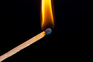 Burning match isolated on black background