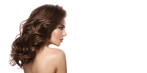 Beauty portrait of a young girl with natural make-up and natural lip color. Hairstyle curls, chestnut hair color. White isolated background.