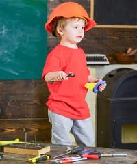 Side view kid standing in workshop. Blond boy in orange helmet holding spanner and handsaw. Little repairman posing for picture