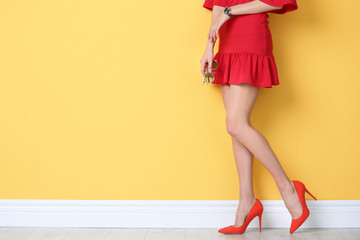 Young woman wearing elegant shoes near color wall, closeup