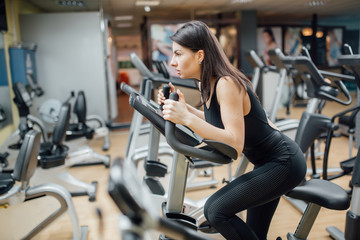 Attractive young woman at the gym riding on spinning bike.Motivation and sporty goal concept