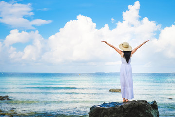 woman traveler enjoying for view of the sea on her holiday.beautiful Asia Lady tourist  in white dress and rise walking on the beach.