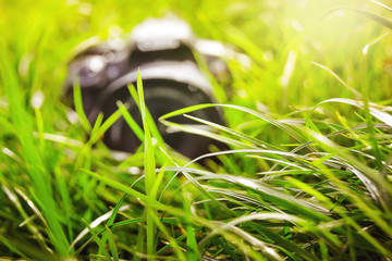 Modern digital camera in  grass. Break during photography_