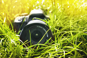 Modern digital camera in  grass. Photographing nature_
