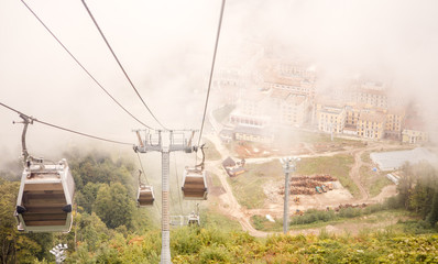 Picture of funicular in mountains against background of misty sky