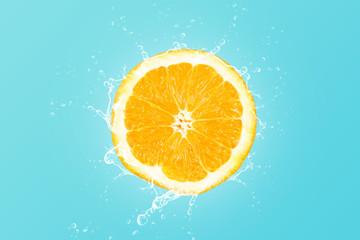 Fresh orange slice with water splash on blue background