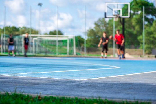 Abstract, blurry background of boys playing basketball in outdoor basketball court in park