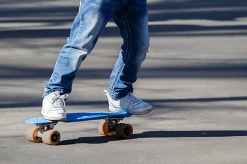 Little the boy in light blue jeans learning to roller skate in summer park. Active outdoor sport for kids. Close up view of legs on skate