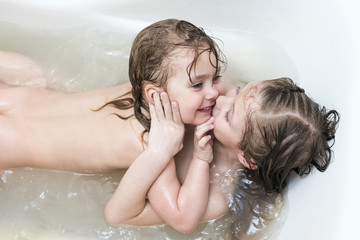 Two wet sisters laugh and hug lying in the bathroom, close-up