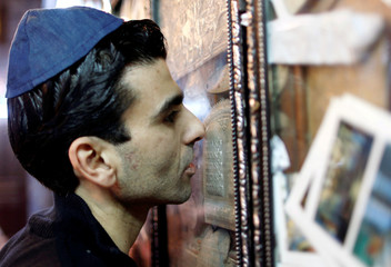 A Jewish man prays and kisses a religious icon at the Ghriba synagogue in Djerba