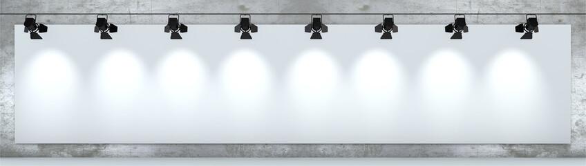 Cartellone pubblicitario bianco, illuminato da faretti appeso ad un muro