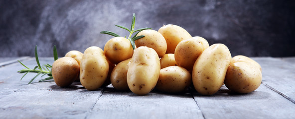 Pile of potatoes lying on wooden boards. Fresh potato