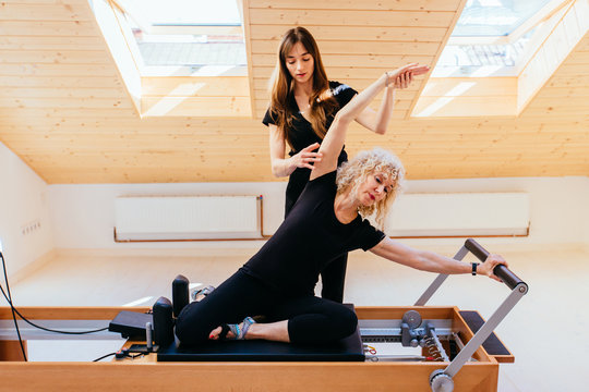Sporty blond curly senior woman doing exercises in gym with help from female physical therapist or instructor.
