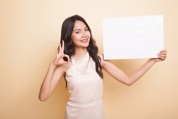 Young Asian woman show OK with  white blank sign.