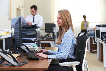 Businesswoman Working At Computer In Busy Office