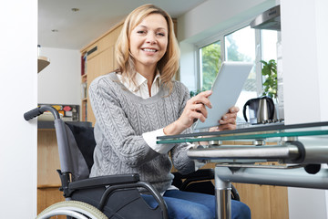 Disabled Woman In Wheelchair Using Digital Tablet At Home