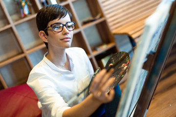 Creative female artist painting new picture