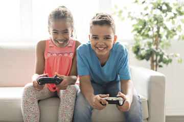brother and sister play video game on sofa
