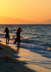 two young women in silhouette on a sunset beach one posing for a photo against a beautiful orange evening sky on the edge of breaking waves