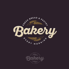 The bakery logo with spikelet. Bread and baking emblem. Vintage bakery logo. Gold and white inscription on a dark background.