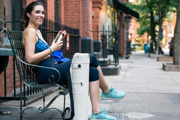 Smiling fit young woman in sportswear holding water bottle while sitting on bench in city