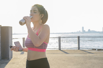 Tired young woman drinking water after workout during sunny day