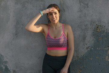 Beautiful tired woman in sportswear looking away while leaning on wall after workout