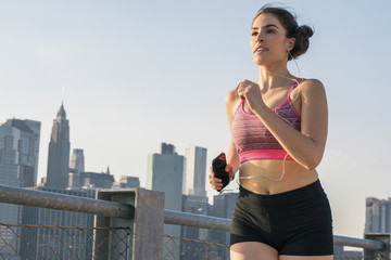Determined young woman holding mobile phone while jogging in city