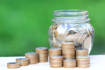 Saving money for prepare in future concept, Stack of coins money and glass bottle on natural green background