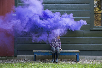 Girl surrounded by purple smoke while sitting outside house